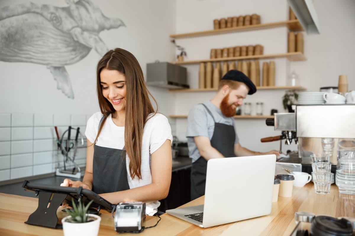 Nhân viên quán cà phê đang giúp khách hàng thanh toán
